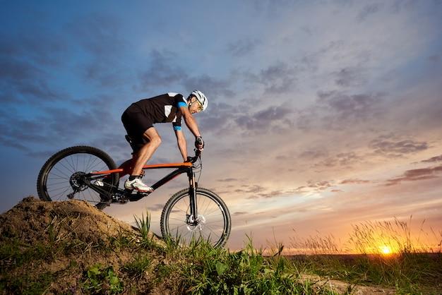 Aktywny rowerzysta jedzie samotnie na rowerze i zjeżdża ze wzgórza. sportowy i solidny mężczyzna na rowerze na tle pięknego zachodu słońca i różowego nieba.
