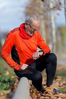 Aktywny senior jogging patrząc na jego zegarek