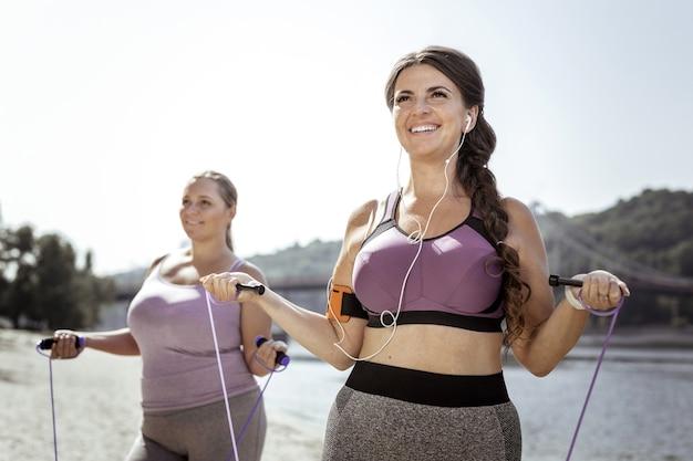 Aktywny sport. szczęśliwa zachwycona kobieta za pomocą skakanki stojąc na plaży ze swoim przyjacielem