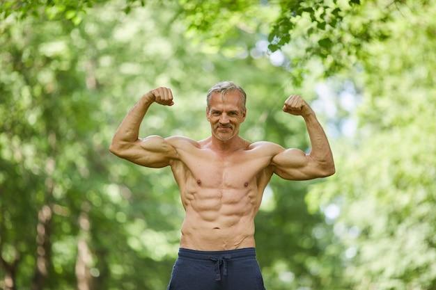 Aktywny, sportowy, starszy mężczyzna stojący bez koszuli gdzieś w parku miejskim, demonstrujący przed kamerą swoje dobrze umięśnione ciało