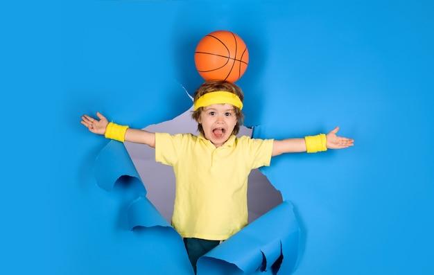 Aktywny sportowy styl życia mały koszykarz zaskoczony chłopiec trzyma piłkę na głowie zajęcia dla dzieci