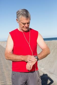 Aktywny starszy człowiek jogging na molo