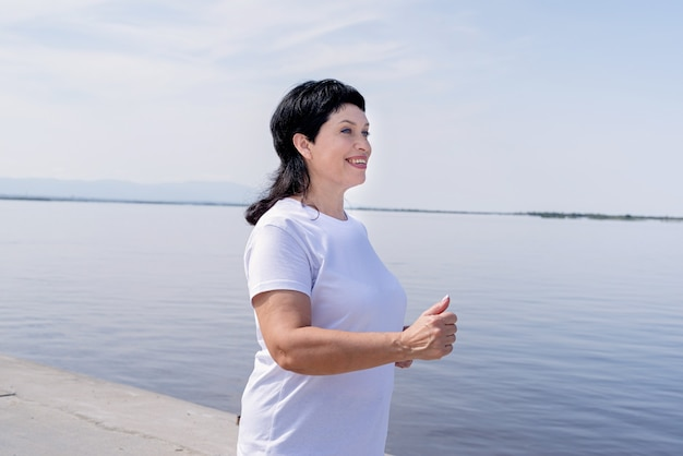 Aktywny starszy kobieta jogging w pobliżu rzeki