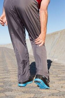 Aktywny starszy mężczyzna dotyka jego rannego kolana