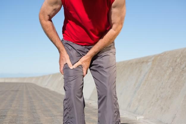Aktywny starszy mężczyzna dotyka jego rannego udo