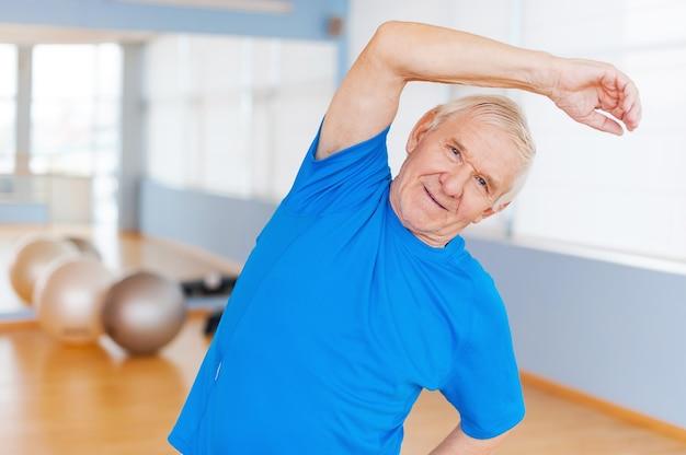 Aktywny starszy mężczyzna. wesoły starszy mężczyzna robi ćwiczenia rozciągające i uśmiecha się stojąc w pomieszczeniu