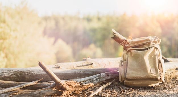 Aktywny styl życia i koncepcja podróży. stary brezentowy plecak na lasowym tle