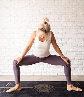 Aktywny styl życia. młoda atrakcyjna kobieta nosi odzież sportową uprawiania jogi w domu. kryty pełnej długości, białe tło ściany z cegły