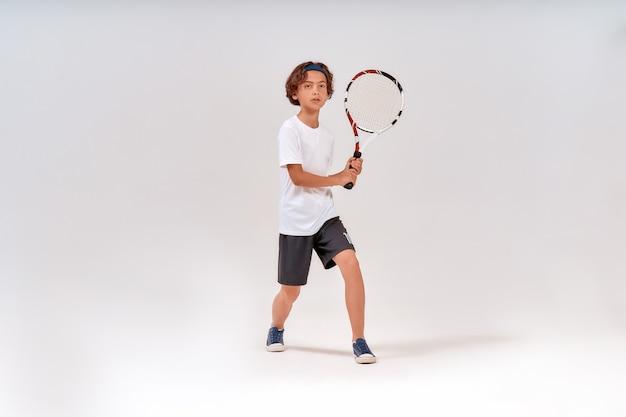 Aktywny styl życia pełnometrażowy strzał nastoletniego chłopca trzymającego rakietę tenisową i odwracającego wzrok na białym tle