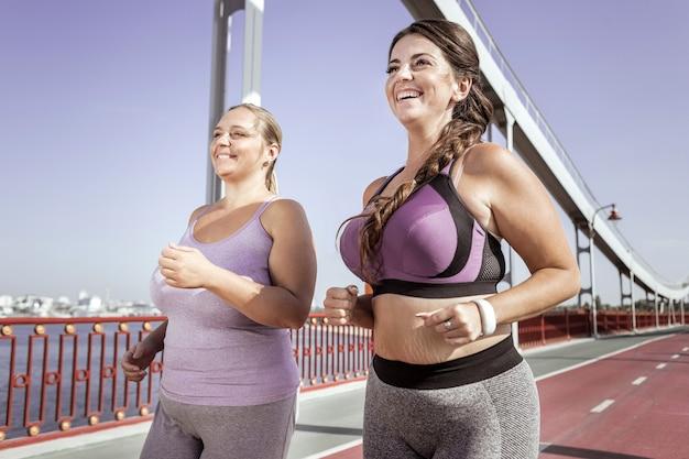 Aktywny styl życia. pozytywne radosne kobiety śmiejące się podczas wspólnego biegu na moście