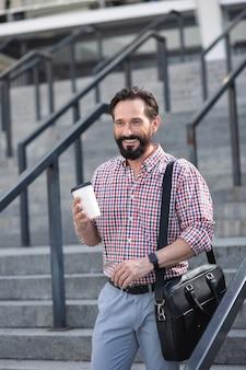 Aktywny styl życia. radosny biznesmen brodaty spaceruje po mieście, wyrażając radość