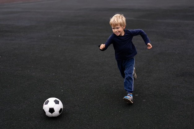 Aktywny styl życia w nowoczesnym mieście - mały chłopiec bawi się piłką nożną na stadionie