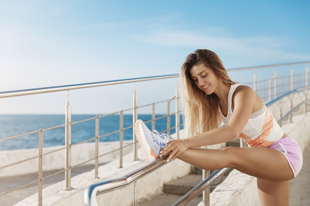 Aktywny stylowy zdrowy lekkoatletyczny młoda kobieta robi poranne ćwiczenia w pobliżu morza, biegając wzdłuż nabrzeża