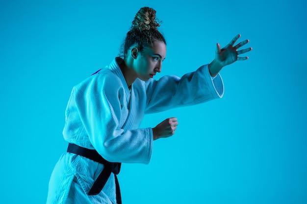 Aktywny trening. profesjonalna judoistka w białym kimono judo, ćwiczenia i szkolenia na białym tle na niebieskim tle neoned studio.