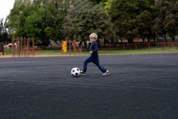 Aktywny tryb życia w nowoczesnym mieście - mały chłopiec bawi się piłką nożną na stadionie