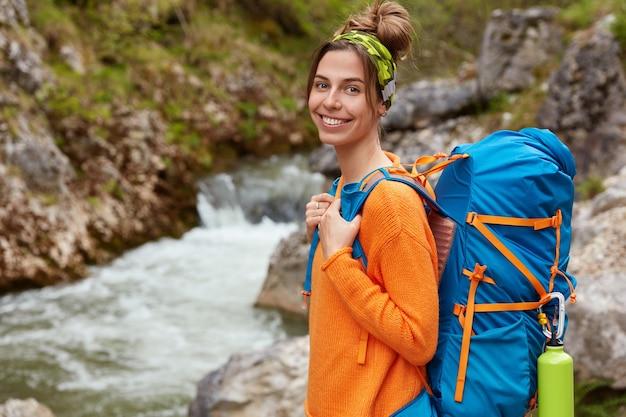 Aktywny wypoczynek i koncepcja pozytywnych emocji. wesoła kobieta ubrana w casualowy pomarańczowy sweter, nosi turystyczny plecak