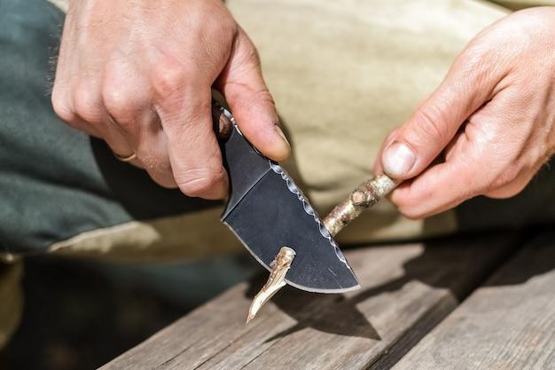 Aktywny wypoczynek na łonie natury mężczyzna struga gałąź drzewa nożem myśliwskim