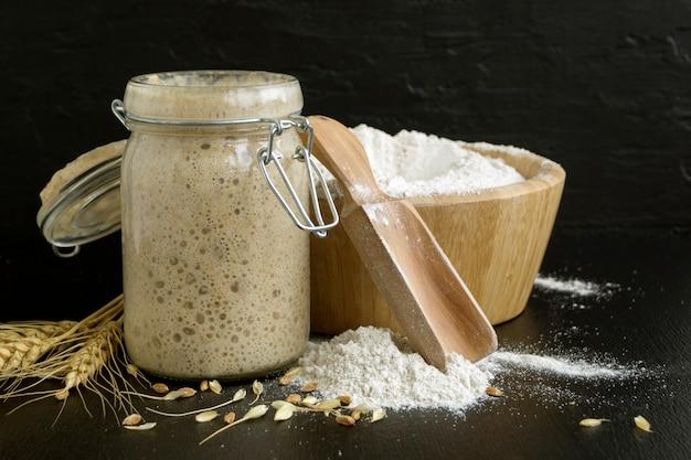 Aktywny zakwas z żyta w szklanym słoiku na domowy chleb.