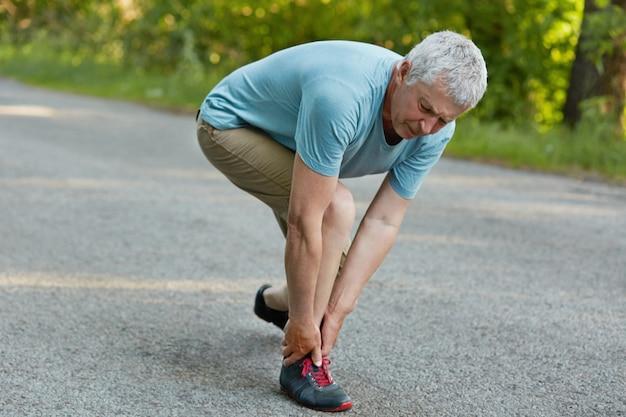 Aktywny zdrowy dojrzały sportowiec stoi bokiem, odczuwa ból nóg po długim joggingu, nosi tenisówki i codzienne ubrania