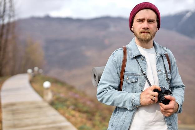 Aktywny zdrowy kaukaski facet z plecakiem i aparatem idzie w kierunku odległej góry. brodaty mężczyzna turysta piesze wędrówki w górach na wiosnę. podróżnik podróżuje po wiejskiej drodze, ekoturystyce, pieszych wędrówkach.