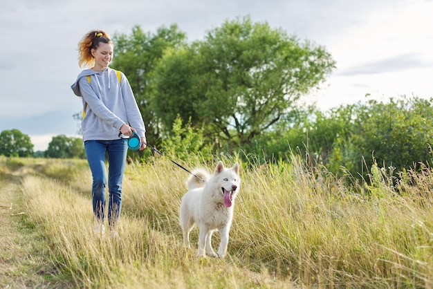 Aktywny zdrowy styl życia, nastolatka spacerująca z białym psem husky, tło piękny krajobraz z niebieskim pochmurnym niebem i żółtą spaloną trawą