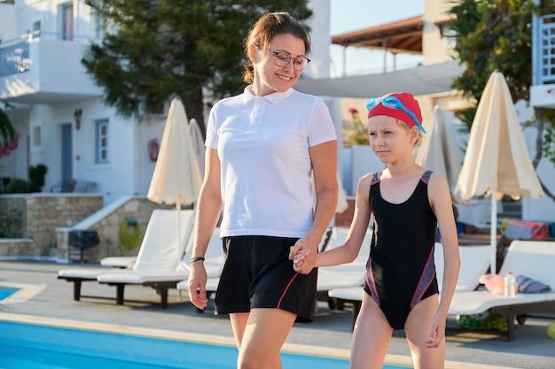 Aktywny zdrowy styl życia u dzieci. trenerka spacerująca z dziewczynką w kapeluszu kąpielowym i goglach na odkryty basen