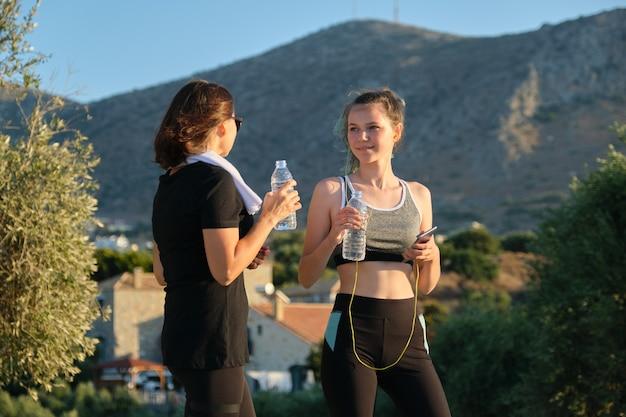 Aktywny zdrowy tryb życia, dwie kobiety - matka i córka nastolatka w sportowej rozmowie i wodzie pitnej po treningu, góry, zachód słońca