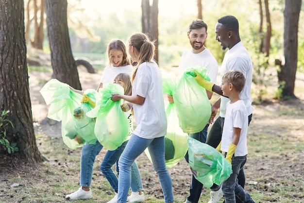 Aktywny zespół międzynarodowych miłośników przyrody w białych podkoszulkach zbierających w lesie śmieci do plastikowych opakowań.