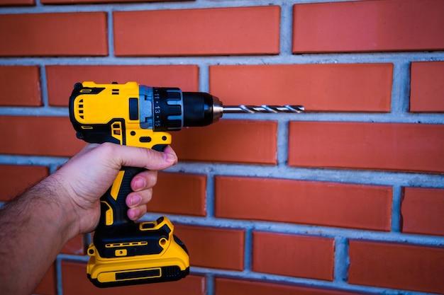 Akumulatorowa wiertarka i wiertarka w rękach człowieka na tle ceglanego muru