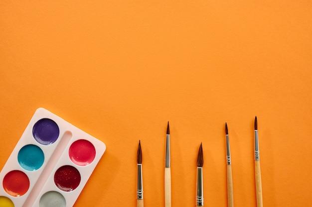 Akwarela farby i pędzle zbliżenie na pomarańczowym tle. artykuły biurowe, akcesoria szkolne lub edukacyjne, narzędzia do pisania i rysowania