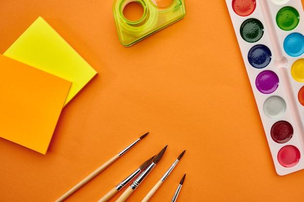 Akwarela farby, pędzle i zbliżenie notatnik na pomarańczowym tle. artykuły biurowe, akcesoria szkolne lub edukacyjne, narzędzia do pisania i rysowania