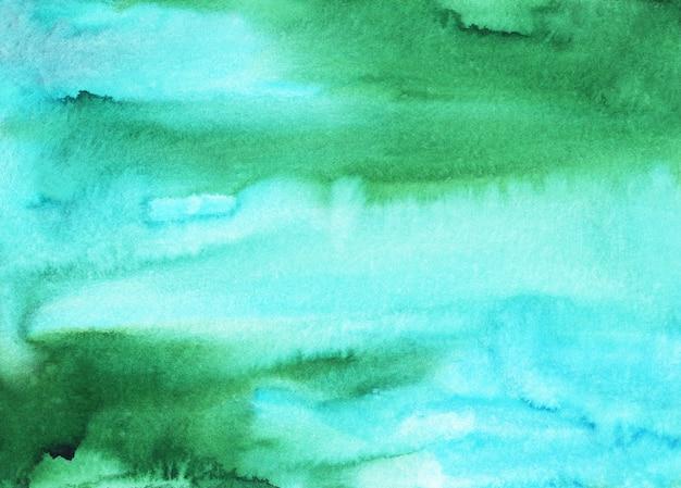 Akwarela jasnoniebieskie i zielone plamy tekstura tło. wielobarwny miękki wodnisty, ręcznie malowany.