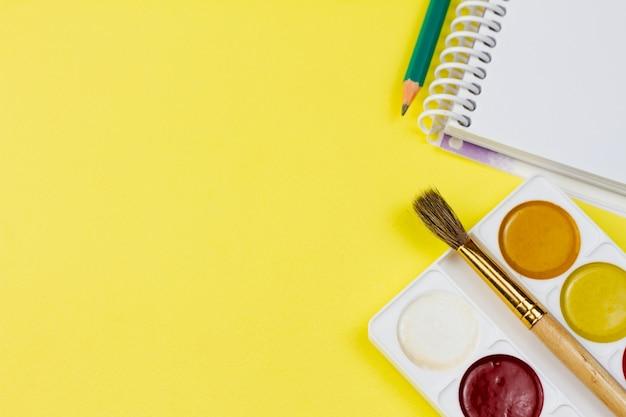 Akwarela z notatnikiem na żółtym tle.