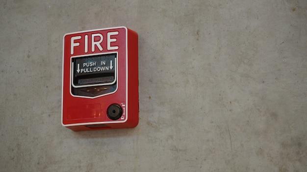 Alarm pożarowy lub urządzenie alarmowe lub dzwonkowe w kolorze czerwonym w budynku dla bezpieczeństwa.
