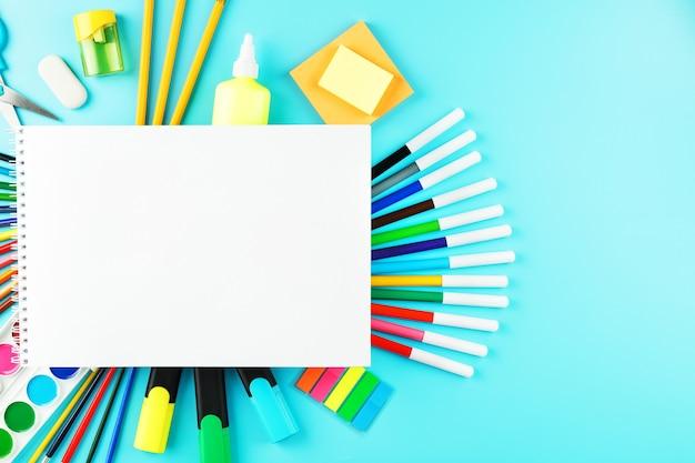 Album do kreatywnego rozwoju w szkole, z papeterią na tle cyjanku. paleta kolorowych farb, markerów, pędzli i ołówków.