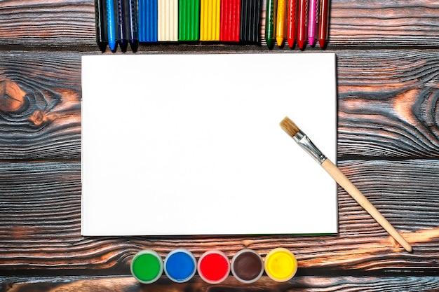 Album do rysowania, pędzel, kredki woskowe, farby na palec i plastelina