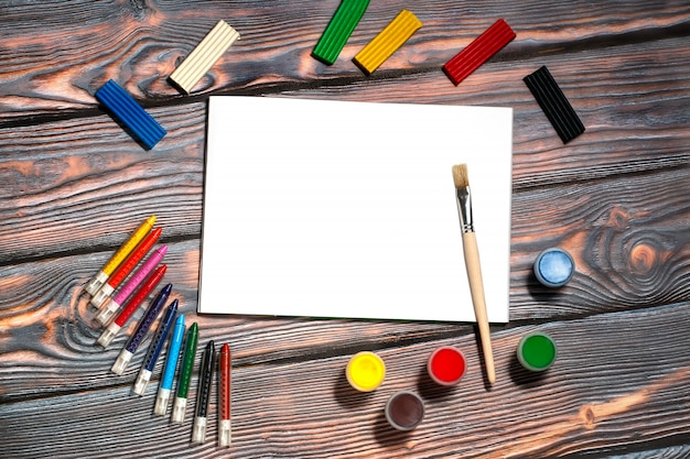Album do rysowania, pędzel, kredki woskowe, farby palcami, plastelina, rustykalne tło