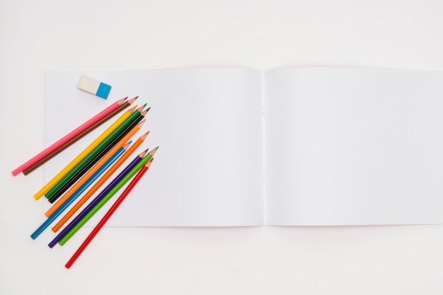 Album rysunkowy i kredki na białym tle. powrót do szkoły