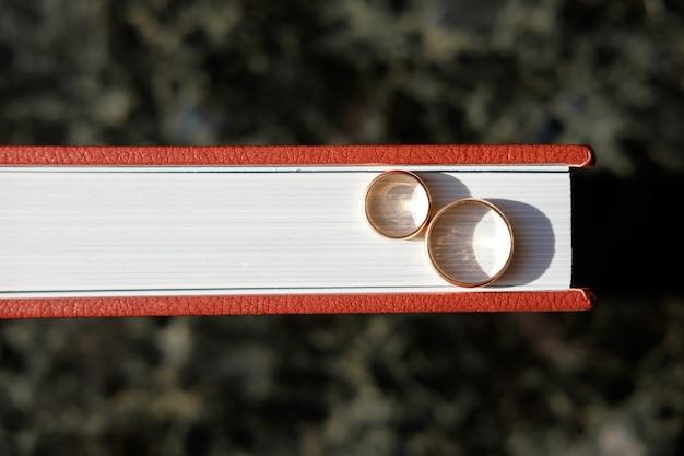Album ślubny pokryty brązową skórą z parą złotych obrączek ślubnych