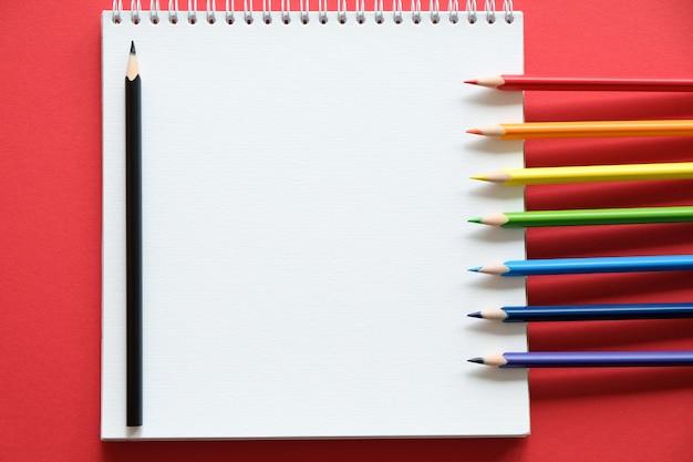 Albumowe i kolorowe kredki na stole. koncepcja kreatywności.
