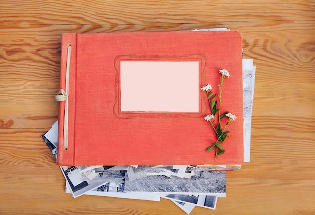 Albumy ze starymi rodzinnymi zdjęciami na drewnianym stole i kwiatach