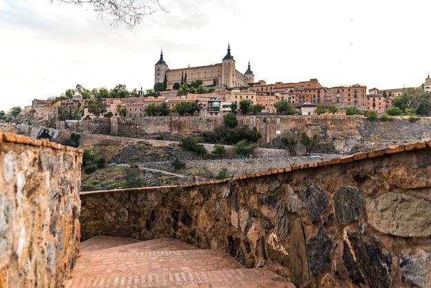 Alcazar i miasto toledo w pochmurny dzień.