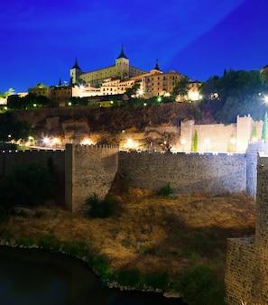 Alcazar od rzeki w nocy. toledo, hiszpania