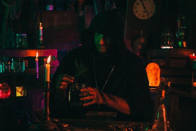 Alchemik w mistycznym laboratorium warzy miksturę. halloweenowy cosplay