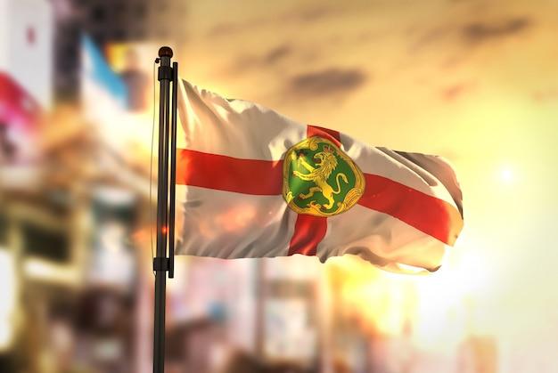 Alderney flag against city zatarcie tła na podświetlenie słońca
