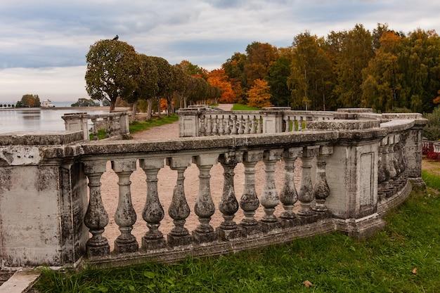 Aleja z betonową klatką schodową pokrytą liśćmi, jesień w parku.