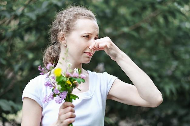 Alergia. kobieta ścisnęła nos dłonią, żeby nie kichnąć z pyłku kwiatów