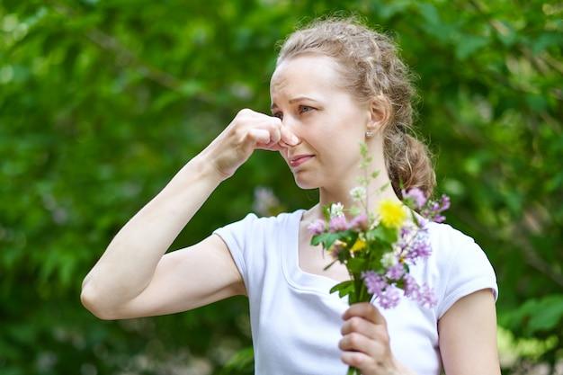 Alergia. kobieta ścisnęła nos ręką, aby nie kichnąć z pyłków kwiatów