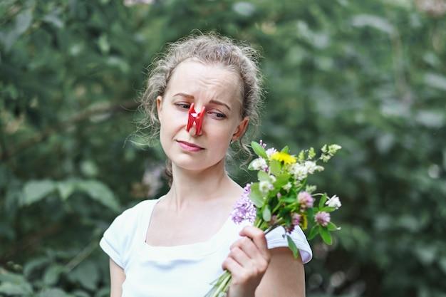 Alergia. kobieta ścisnęła nos spinaczem do bielizny, aby nie kichnąć z pyłku kwiatów