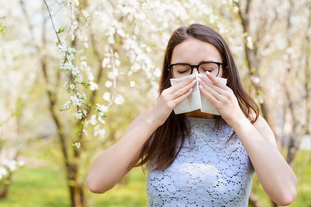 Alergiczna kobieta dmuchająca nosem w białą chusteczkę na tle kwitnących drzew w parku na wiosnę